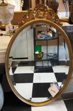 $295 Gold, oval mirror with bow at the crown. Beveled edge.