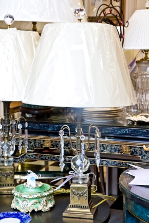 Pair of ornate carved metal regency lamps with decorative cut crystal ball and base and large hanging cut crystal pendants. Linen shades and cut crystal ball finials