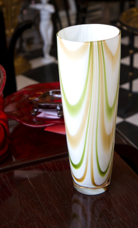 $45 White cased glass vase with green and beige swirls.