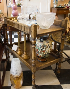 $535. Flemish style two-tiered oak drinks cart on casters. Baluster turned legs and carved gallery