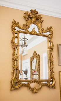 $1,495. Elaborately carved gilt wood beveled mirror decorated with scrolling and leaf details, surmounted by a floral bouquet. Mirrors set between the gilt wood elements.
