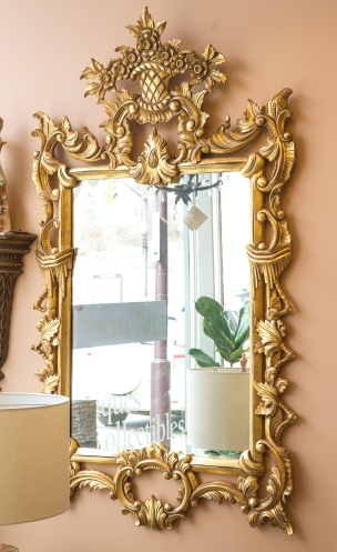 $925. Elaborately carved gilt wood mirror decorated with scrolling and leaf details, surmounted by a floral bouquet.