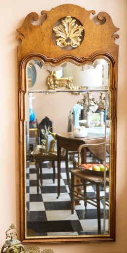 $1,250. George I style walnut mirror with shaped beveled glass in carved frame with gilt accents.